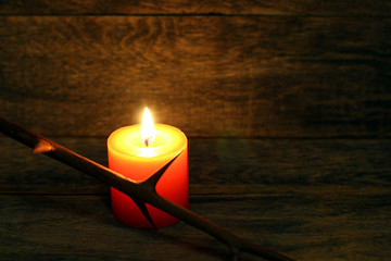 Prickly branch and burning candle on wooden background. Copyspace