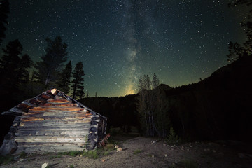 The milky way rises over an old log cabin in the wilderness of California Wall mural