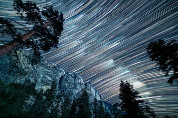 Long star trails of the milky way pass over the top of Kern canyon in a long exposure showing the granite cliffs and pine trees Fototapete