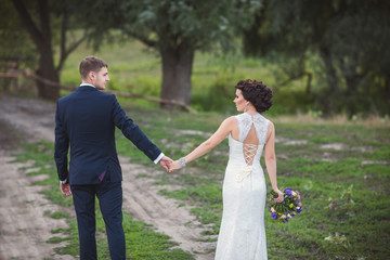 Newlyweds couple holding hands and walking outdoor after their wedding ceremony