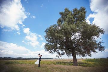 Bride and groom hugging near tree