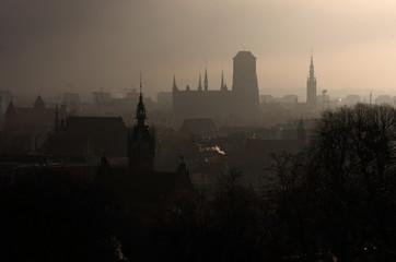 Miasto we mgle, wschód słońca.