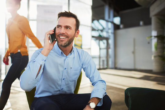 Handsome businessman talking on the phone during coffee break in