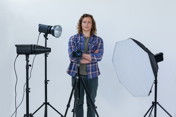 Photographer with hands crossed standing in the photo studio
