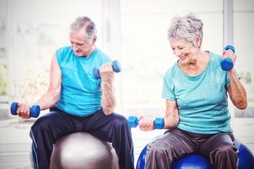 Smiling senior couple holding dumbbells while exercising