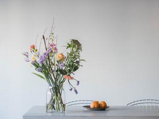 bunte Blumen in Glasvase auf dem Tisch und Orangen