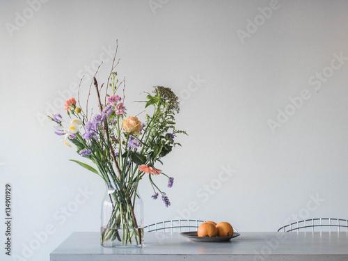 bunte blumen in glasvase auf dem tisch und orangen. Black Bedroom Furniture Sets. Home Design Ideas