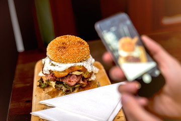 Delicious burger. Photographing burger with smart phone.