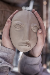 Human hands holding clay face