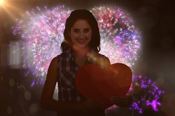 Composite image of portrait of smiling woman holding heart card