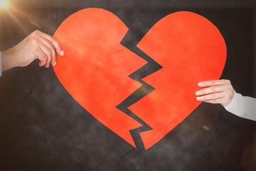 Composite image of couple holding broken heart shape paper