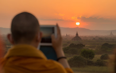 Buddhist monk travel and take a photos of beautiful sunset over the ancient temple in Bagan plains of Myanmar.