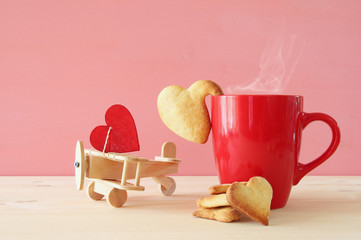 Wooden plane with heart next to cup of coffe
