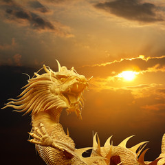 Golden chinese dragon on sky at sunset.