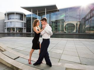 two young people - a man in white shirt and a woman wearing black dress - dancing outside on city embankment against modern glass buildings