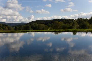 Lake in the bavarian forest with mirrored cloudy sky