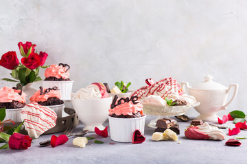 Beautiful chocolate cupcake, pink cream, meringue cookies and red roses on gray stone background. Valentines, Mother Day, wedding concept with copy space.