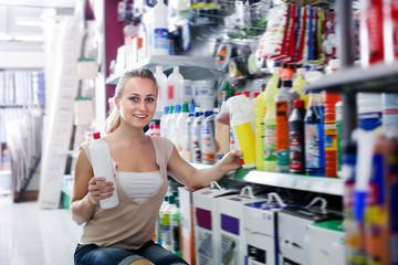 Portrait of glad female customer taking bottle