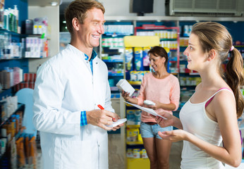 Glad man pharmacist helping customers