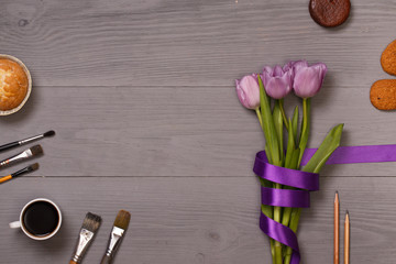 Lilac tulips and coffee with biscuits in the lilac wooden table of the artist. Banner template layout mockup for Woman Day, Valentines Day and Teacher's Day.
