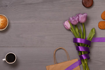 Lilac tulips and coffee with biscuits in the lilac wooden table. Banner template layout mockup for Woman Day, Valentines Day and Teacher's Day.