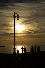 Embankment of the Italian city of Trieste, the sea and the sunset is necessary to see the silhouette of the tourists.