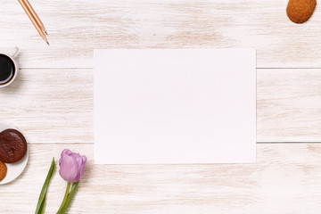 Banner space for text. White wooden table. Lilac tulip at the desk.