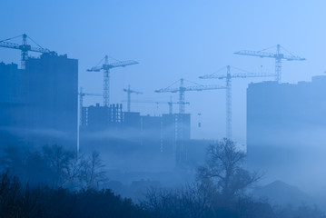 Cranes over new buildings in the early foggy morning.