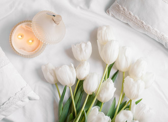 Spring flowers tulips with candles and white pillows