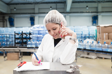 Young happy woman worker in factory for water bottling and packing writing something, making inspection quality control and talking on her cell phone. People at work.
