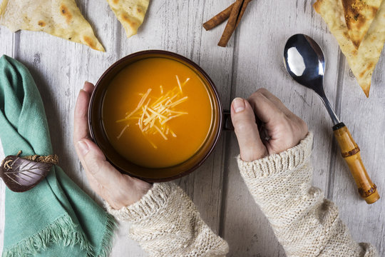 Hands holding bowl with homemade soup on wooden table, top view