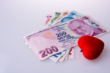 Turkish Lira banknotes by the side of a red color heart shaped o