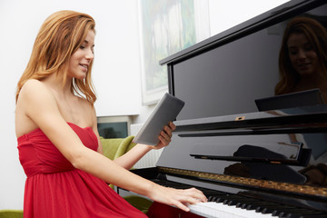 beautiful Woman use tablet and playing piano music