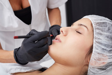 professional tattooist making permanent make up on lips