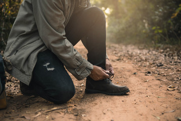 Hikers muddy boots on forest trail. Young man athlete tying up laces on his shoes on autumn forest path.