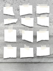 Multiple blank ripped pieces of paper frames with adhesive tape on gray weathered marble stone wall
