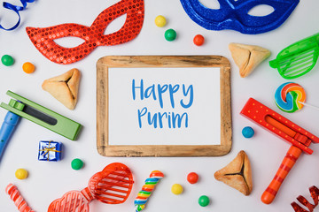 Jewish holiday Purim concept with hamantaschen cookies, carnival mask and photo frame on white background. View from above