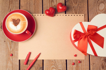 Valentines day concept with greeting card, gift box and coffee cup over wooden background. Top view from above