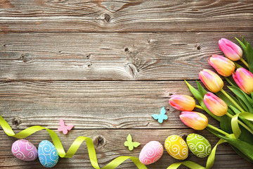 Easter background with colorful eggs and spring tulips