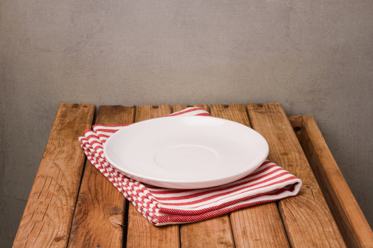 Background with empty plate on tablecloth and wooden table over rustic wall