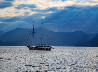 Vintage ship sailing with sun rays.