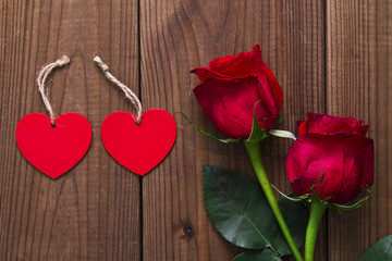 Label and red roses on wooden background