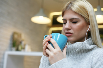 Female student listening music and drinking coffee.