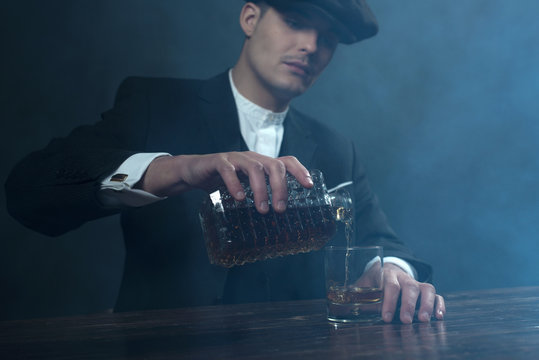 Retro 1920s english gangster with flat cap pouring whiskey. Peak