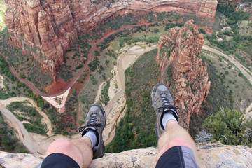 First person perspective shot from a hiker sitting at the edge of a cliff at Angel's Landing in Zion National Park. Wall mural