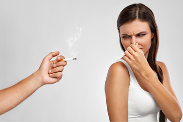 Smoking. Beautiful Woman Holding Nose, Smelling Cigarette Smell