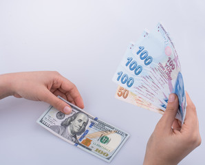 Hands holding American dollar banknotes and Turksh Lira banknote