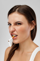 Portrait Of Girl With Cigarette In Mouth And Grimace On Face