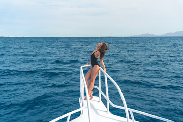 The beautiful woman stand in the yacht on the sea background