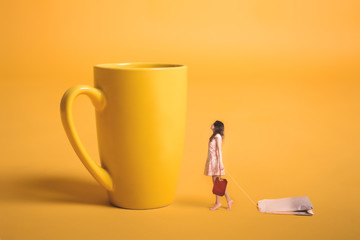 Obraz Surrealism design. Girl holding a tea bag in his hand. Miniature people. Yellow empty cup on a yellow background. Young girl makes tea. - fototapety do salonu